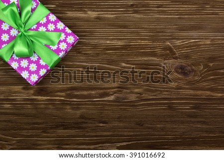 Gift box with ribbon on wooden table - stock photo