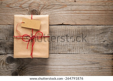 Gift box with tag on wooden background - stock photo