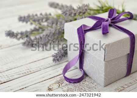 Gift box with violet ribbon and bouquet of lavender on wooden background - stock photo