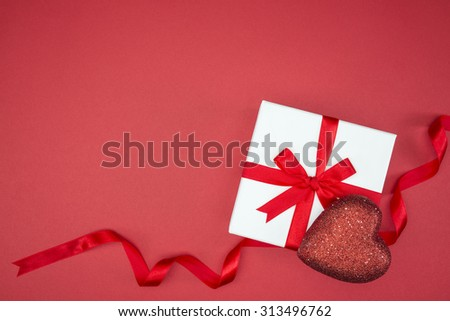 gift box wrap silk ribbon with love heart shape on red background