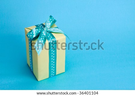 Gift box wrapped in apple green paper, tied with a teal polka dot bow, against a bright teal-colored background. - stock photo