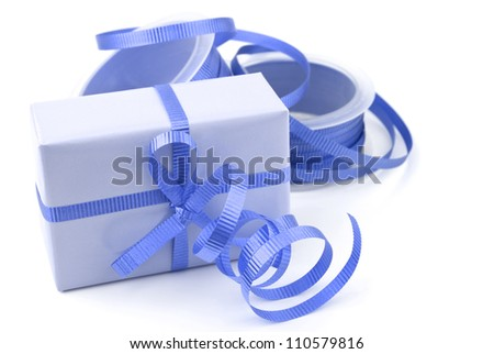 Gift box wrapped in blue wrapping paper and curly ribbon isolated on white background. - stock photo