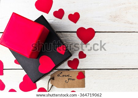 Gift boxes and heart paper cut with craft label and love confession on white wooden background. Valentines day. - stock photo