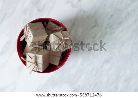 Gift boxes in red bucket on white marble background, Christmas and New Year concept. copy space.