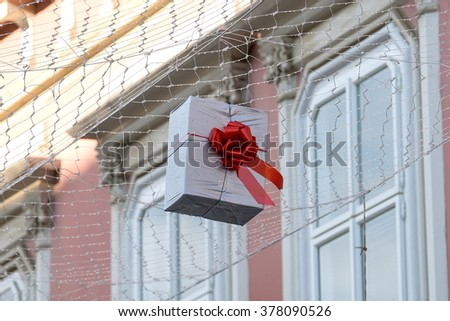Gift boxes that hang suspended on wires and networks. Street decorations before Christmas, New Year and Valentine's Day. - stock photo