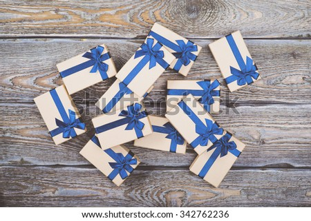 Gift boxes with blue ribbons on dark wooden background - stock photo