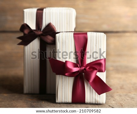 Gift boxes with colorful ribbon on wooden background - stock photo