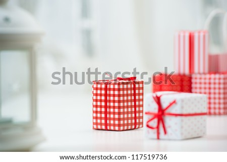 Gift boxes with xmas presents wrapped in red paper with ornament. Lots of copyspace - stock photo
