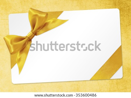 gift card with golden ribbon bow Isolated on yellow background - stock photo