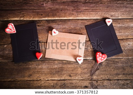 Gift Cards on wooden background with cookies in the shape of heart and red ribbon