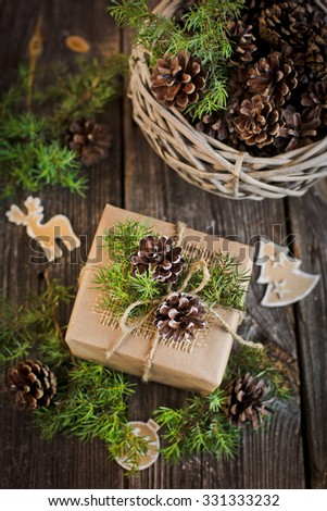 gift decorated with pine cones on the wooden background - stock photo