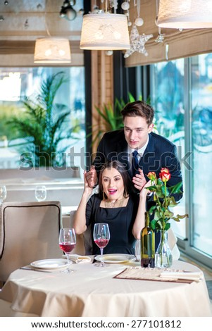 Gift for a loved one. Romantic dinner in the restaurant. Young couple sitting at a table in the restaurant until the guy opened the girl her eyes with his hands - stock photo