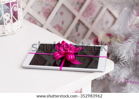 Gift for the holidays tablet with a bow - stock photo