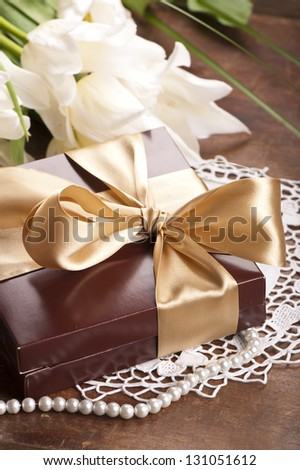 gift in a box with a bow and flowers white tulips on a wooden table - stock photo
