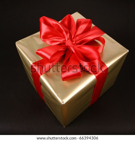 Gift in golden wrapping with red bow isolated on black background - stock photo