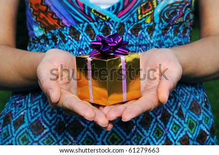 Gift in womans hand. outdoor.