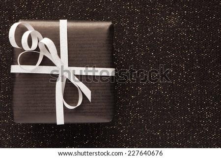 Gift on black shiny background. - stock photo