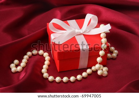 gift on red silk satin background. - stock photo