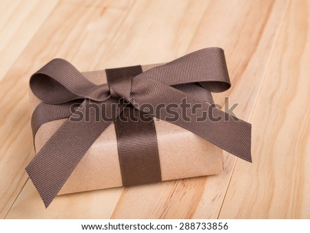 Gift package wrapped in ribbon and bow on wood surface - stock photo