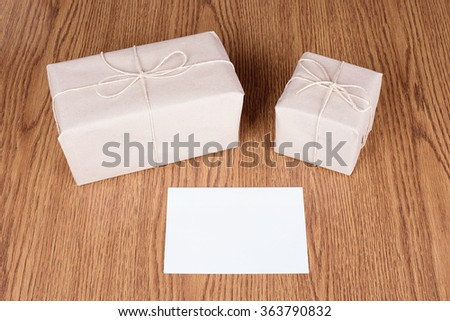 Gift packages wrapped in brown recycled paper on wooden background - stock photo