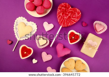 Gift set for Valentines Day with box, sweets and candles on purple background