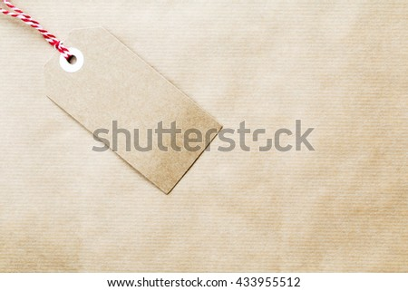 Gift tag made of brown card at an angle on brown paper with red and white decorative string and copy space for a custom message