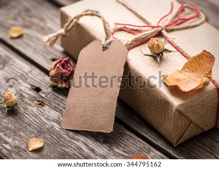 Gift tag with gift box on a vintage wooden background. Close-up shot. - stock photo