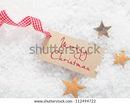 Gift tag with Merry Christmas greeting and a decorative red and white checked ribbon on a bed of winter snow with stars - stock photo