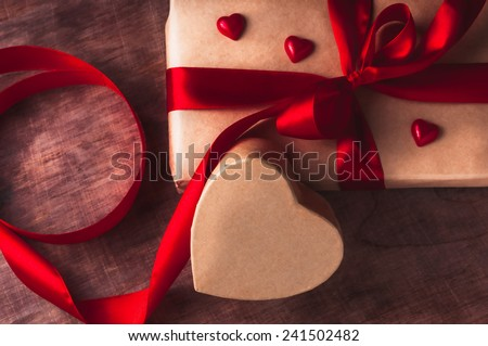 Gift tied with ribbon and red heart on  wooden background. Valentine's day. - stock photo