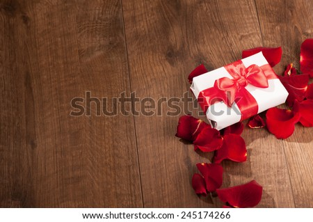 Gift to Saint Valentines Day. Top view image of white present box with red ribbon on top decorated with rose petals on wooden background with copy space - stock photo