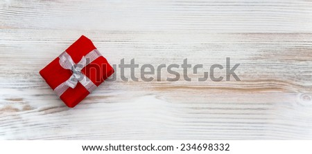 Gift with decorated package on wooden background - stock photo