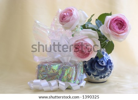 Gift with nice bow and roses in a beautiful vase