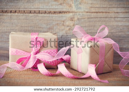 gift with pink ribbon and band on wooden background - stock photo