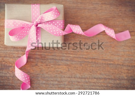 gift with pink ribbon,heart and band on wooden background - stock photo