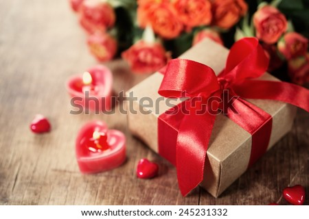 Gift with red bow and heart-shaped candles on the wooden background, Valentines - stock photo
