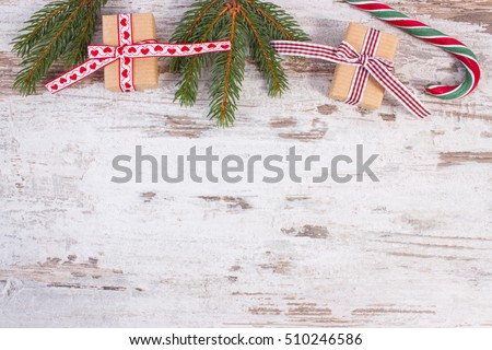 Gift wrapped in old vintage paper tied colorful ribbon, candy cane and green spruce branches, wooden rustic background, copy space for text