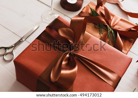 Gift wrapping background. Packaging stylish christmas present boxes in maroon paper decorated with satin ribbon bows. Christmas and winter holidays concept. Still life