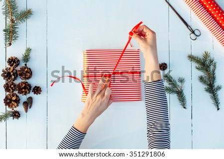 Gift wrapping. Woman packing gifts, step by step - stock photo