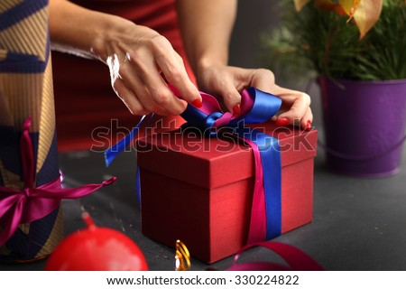Gift wrapping. Woman packs gifts, step by step  - stock photo