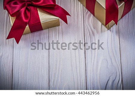 Giftboxes with tied bows on wood board holidays concept. - stock photo