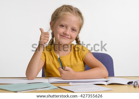 Gifted child demonstrates that she loves to get knowledge with the OK gesture and adorable smile. Nice picture for wallpaper with little girl having positive emotions and attitude towards education. - stock photo