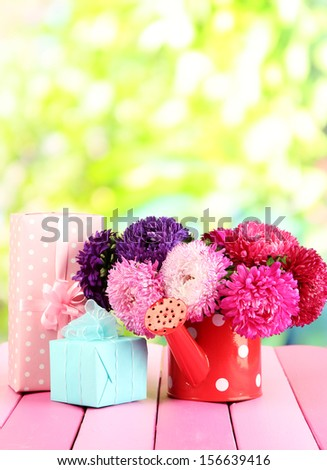 Gifts and flowers in watering can, on nature background - stock photo
