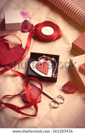 Gifts and heart shape toys with rose petals ready for wrapping on Valentine's day