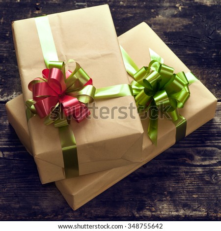 Gifts boxes on the old dark boards. Christmas background. Christmas decorations. New Year background. Xmax background. Selective focus on a bow-knot. Small depth of field. Toned image. - stock photo