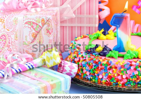 Gifts, noise makers, balloons surround a beautiful birthday cake with a lit number one candle. - stock photo