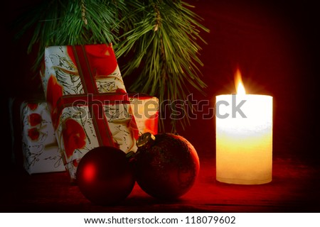 Gifts under the Christmas tree next to a candle - stock photo