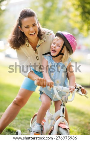 Giggles make the world go around! Summer time in the city park... A mother and daughter laugh together as the mother teachers her blonde, blue-eyed daughter how to ride her bike.  - stock photo