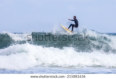 GIJON, SPAIN     August 31 2014:  Young athletes surfing on a beach located on the outskirts of Gijon. Spain. August 31, 2014 - stock photo