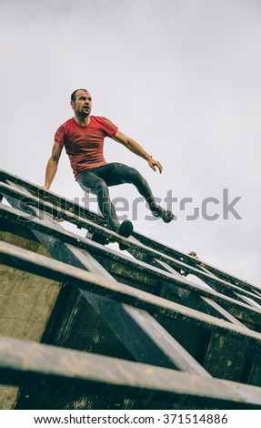 GIJON, SPAIN - JANUARY 31, 2016: Runner into the Farinato Race event, a extreme obstacle race, celebrated in Gijon, Spain, on January 31, 2016. Man going down a wooden wall in a test of the race. - stock photo