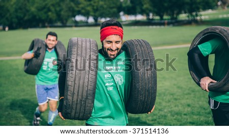 GIJON, SPAIN - JANUARY 31, 2016: Runners into the Farinato Race event, a extreme obstacle race, celebrated in Gijon, Spain, on January 31, 2016. Portrait of runner carrying tires in test of the race. - stock photo